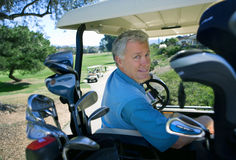 Mature man driving golf buggy on golf course, looking over shoulder, smiling, rear view, portrait Stock Photography