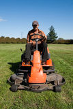 Mature man driving grass cutter. In a sunny day Stock Photography