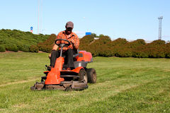Mature man driving grass cutter. In a sunny day royalty free stock image