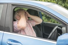 Mature man driving in his car looking fed up. And frustrated stock photo