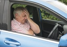 Mature man driving in his car looking fed up. And frustrated stock photography