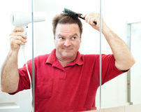 Mature Man Drying His Hair. Mature man blow drying his hair in the bathroom mirror Royalty Free Stock Images
