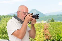 Mature man with dslr camera, outdoors Royalty Free Stock Photos