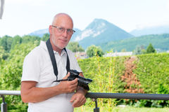 Mature man with dslr camera, outdoors Royalty Free Stock Images