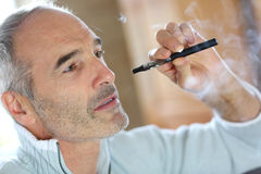 Mature man with an e-cigaret at home Royalty Free Stock Photography