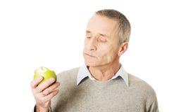 Mature man eating an apple. Mature man eating healthy apple royalty free stock photos