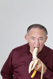 Mature man eating banana Stock Photo