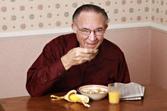 Mature man eating breakfast Stock Photo