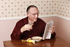 Mature man eating breakfast Royalty Free Stock Images