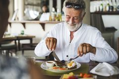 Mature man eating breakfast at hotel royalty free stock photography