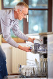 Mature man empty out the dishwasher. Modern ambience Royalty Free Stock Images