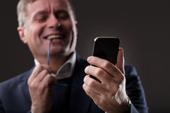 Mature man enjoying digital content online. Mature man blurred in the background watching or reading something funny on his mobile phone in focus Royalty Free Stock Images