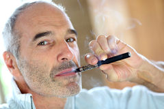 Mature man enjoying e-cigarette Stock Photos