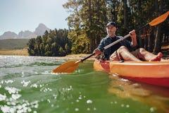 Mature man with enjoying kayaking in a lake. Portrait of a mature man with enjoying kayaking in a lake. Caucasian man wearing a cap paddling a kayak on summer royalty free stock images