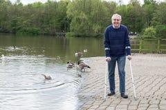 Mature man enjoying walk by lake, walking with crutches Stock Photos