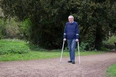 Mature man enjoying walk, walking with crutches Stock Photos