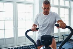 Mature man exercing on a stationary bike at the gym stock image