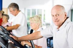 Mature man exercising. Mature older man exercising in the gym stock photos