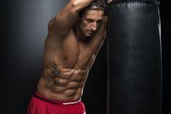 Mature Man Exercising Bag Boxing In Studio Stock Images