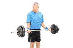 Mature man exercising with a heavy barbell Stock Photography