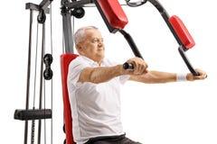 Mature man exercising on a multifunctional machine Royalty Free Stock Image