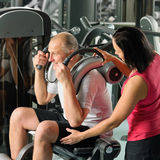 Mature man exercising with personal trainer Royalty Free Stock Photos