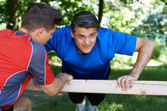 Mature Man Exercising With Personal Trainer In Park Stock Photo