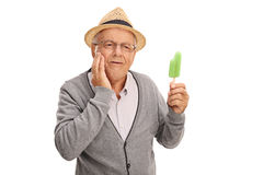 Mature man experiencing tooth ache. Mature man experiencing a tooth ache from eating ice cream isolated on white background Royalty Free Stock Photography