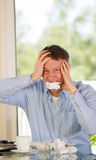 Mature man expressing rage at work. Mature man showing stress by biting wad of paper while working from home with bright daylight coming in from window in Stock Photography