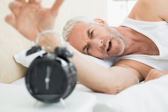 Mature man extending hand to alarm clock in bed Royalty Free Stock Photo