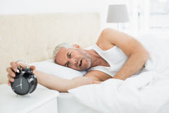 Mature man extending hand to alarm clock in bed Stock Image