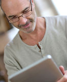 Mature man with eyeglasses reading ebook Stock Photos