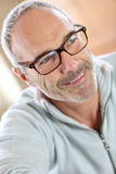 Mature man with eyeglasses relaxing at home Stock Images