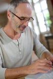 Mature man with eyeglasses using keyboard Stock Image