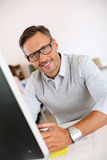 Mature man with eyeglasses working with computer Royalty Free Stock Photos