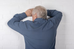 Mature man facing a wall Stock Photos