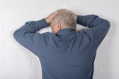 Mature man facing a wall Stock Images