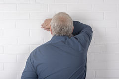 Mature man facing a wall Stock Photo