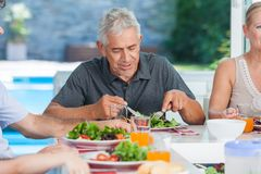 Mature man with family dinner table Royalty Free Stock Photography