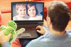 Mature man father lying on sofa and communicate trough video call on laptop with his kids, a little boy and girl showing them toys. Rear view of dad relaxing on royalty free stock images