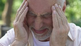 Mature man feeling sudden sharp pain in head, migraine attack, risk of thrombus