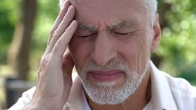 Mature man feeling sudden sharp pain in head, migraine attack, risk of thrombus. Stock photo stock images
