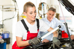 Mature man and female car mechanic in workshop Stock Images