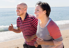 Mature man and female jogging along the sea royalty free stock images
