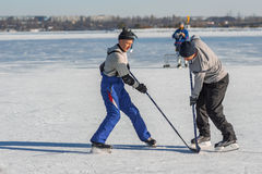 Mature man fighting for the pack while playing hockey on a frozen river Dnepr. Dnepr, Ukraine - January 22, 2017: Mature man fighting for the pack while playing stock photography