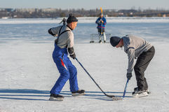 Mature man fighting for the pack while playing hockey on a frozen river Dnepr. Dnepr, Ukraine - January 22, 2017: Mature man fighting for the pack while playing stock photos