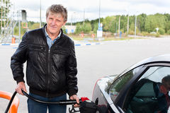 Mature man filling car with gasoline in Stock Photo
