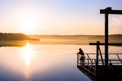 Mature man fishing on quiet lake at summer sunrise stock photography
