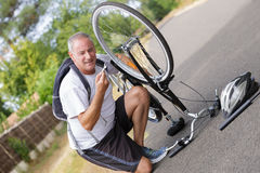 Mature man fixing bike outdoors. Mature man is fixing his bike outdoors Royalty Free Stock Photos