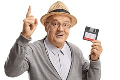 Mature man with a floppy disk holding his index finger up Stock Photos